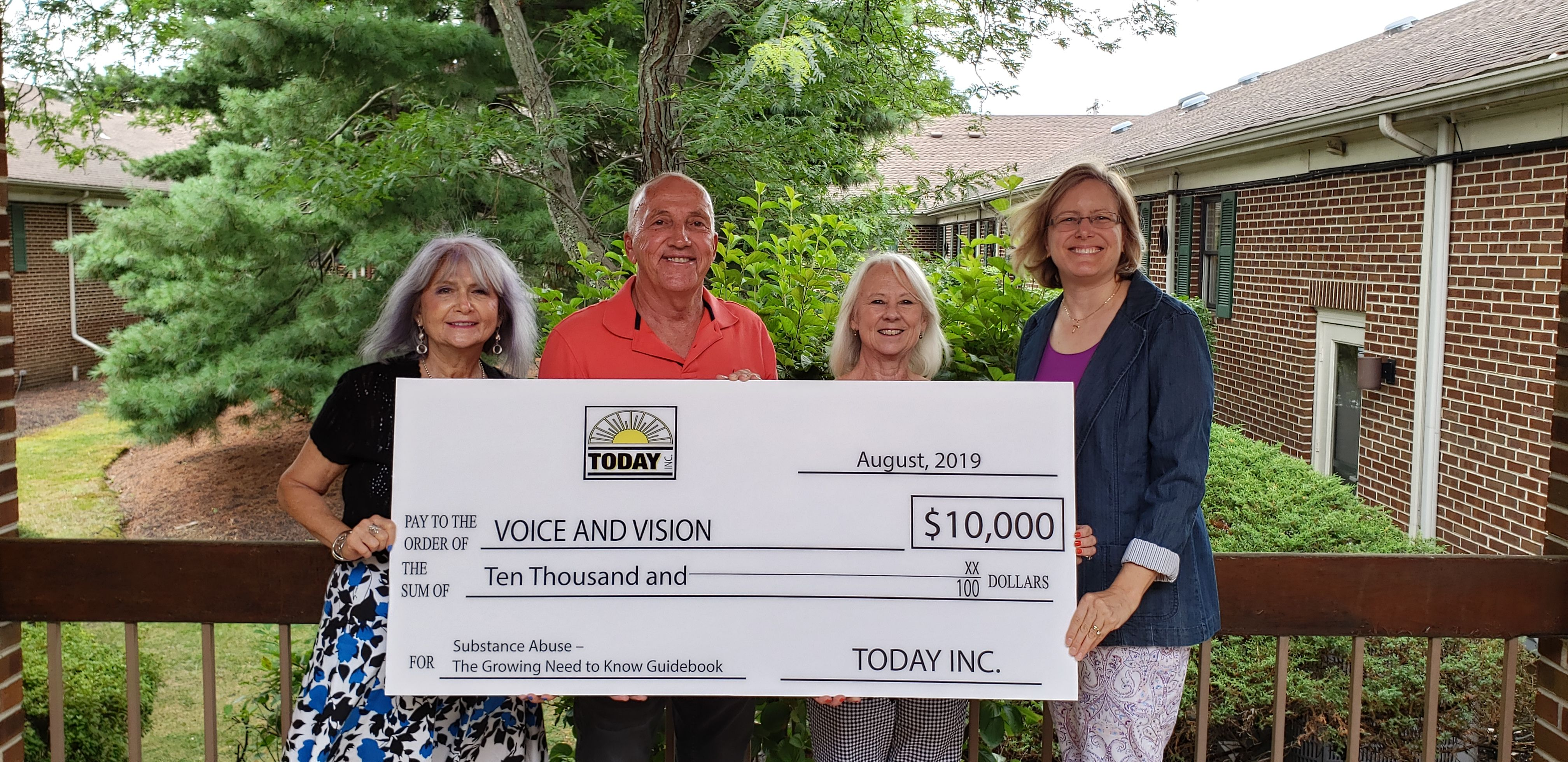 Pictured from left to right with the check: Valerie Melroy (Voice and Vision, Inc., CEO), John Howell (Executive Director, Today, Inc.), Karen Plummer (Guide Producer) and Maria Miller (Guide Editor)